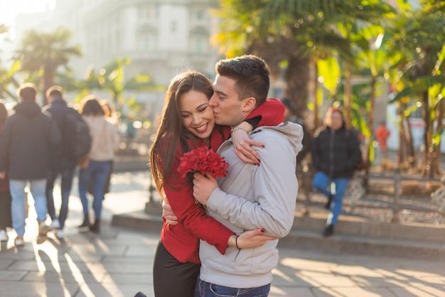 Hombre dando flores y besando a su novia