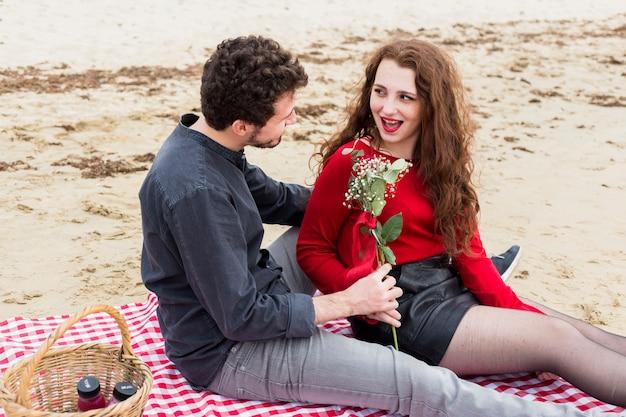 Hombre dando flores a mujer en colcha