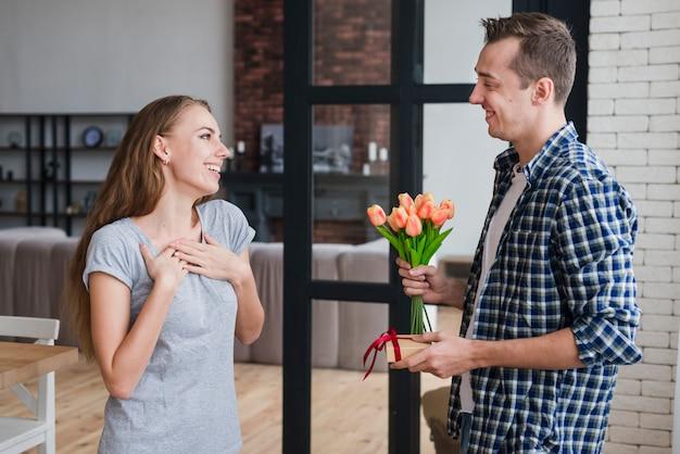 Hombre dando flores y regalo a su esposa.
