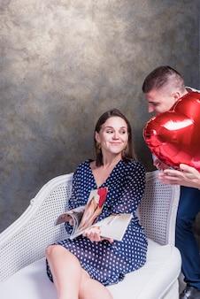 Hombre dando globo de corazón rojo a mujer