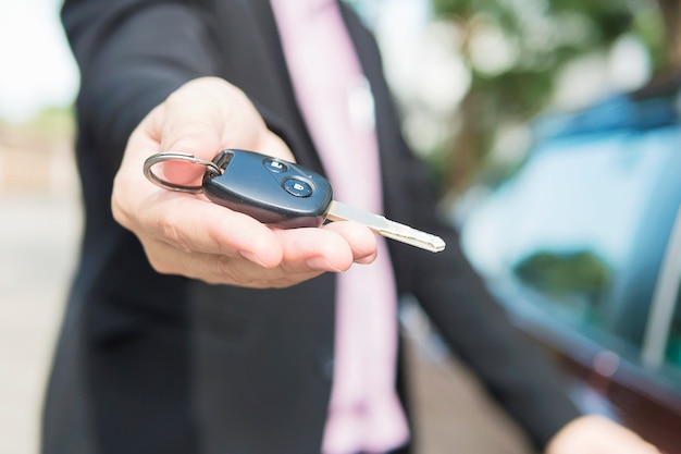 El hombre le está dando la llave de un auto a alguien.