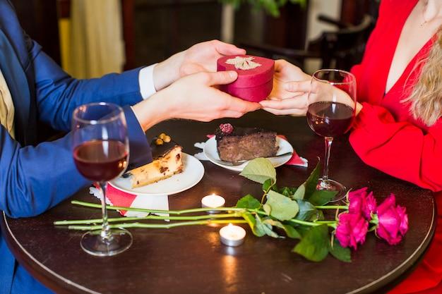Hombre dando una pequeña caja de regalo a la mujer en la mesa en el restaurante
