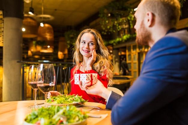 Hombre dando una pequeña caja de regalo a una mujer rubia en la mesa