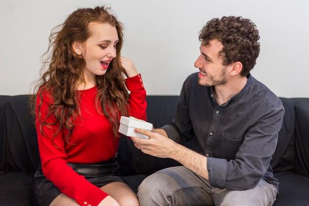Hombre dando una pequeña caja de regalo a la mujer en el sofá