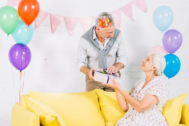Hombre dando regalo de cumpleaños a su esposa sentada en el sofá