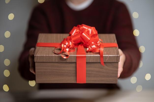 Hombre dando un regalo de navidad decorado con cinta roja