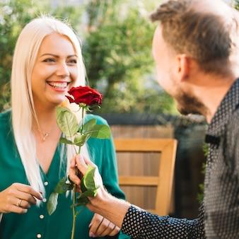 Hombre dando rosa roja a su novia al aire libre