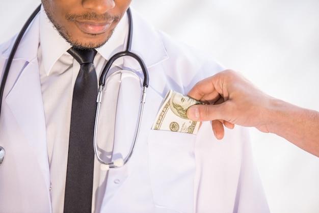 Hombre dando soborno médico en la clínica.