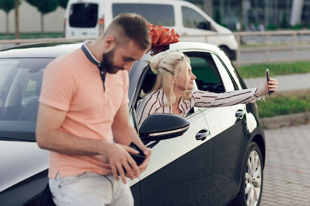Hombre dando sorpresa a la mujer comprando un coche nuevo. mujer joven feliz sentada detrás del volante y tomando un selfie.
