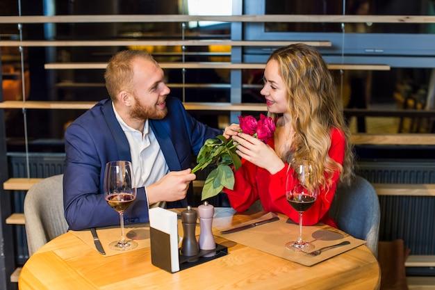 Hombre, dar, ramo de rosas, a, mujer, en la mesa
