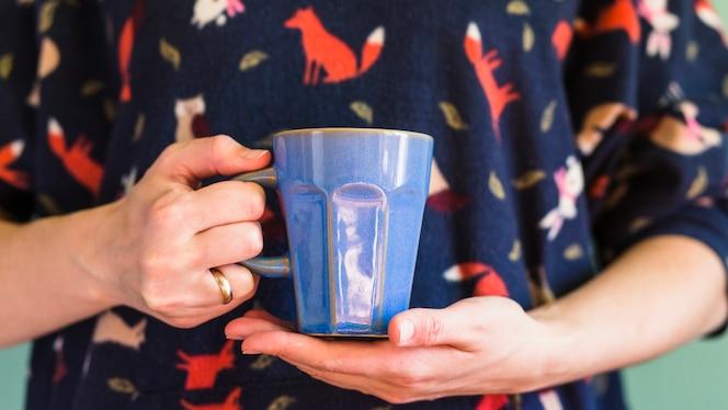Hombre de cosecha que sostiene la taza azul