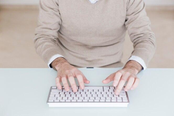 Hombre de cultivos usando el teclado de la computadora