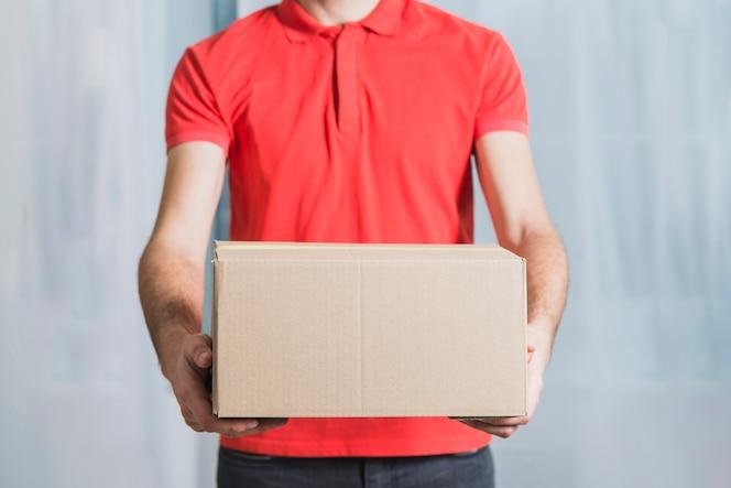 Hombre de entrega de cultivos mostrando paquete