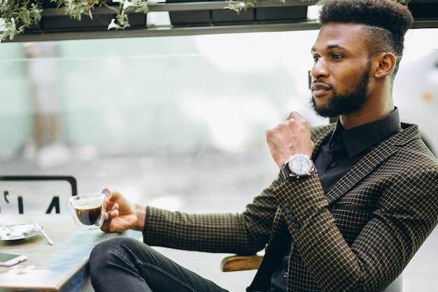 Hombre de negocios afroamericano en un café tomando café