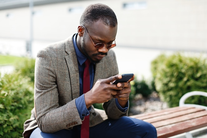 Hombre de negocios afroamericano trabaja en su teléfono inteligente sentado en el banco fuera