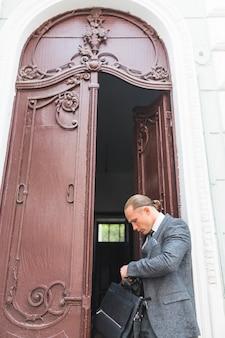 Hombre de negocios con la bolsa del ordenador portátil que se coloca cerca de puerta abierta
