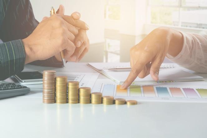 Hombre de negocios con la reunión y el análisis de la empresaria para el negocio con las monedas de la pila.