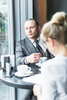Hombre de negocios con taza de café sentado en el restaurante