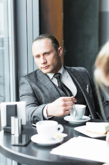 Hombre de negocios contemplado con taza de café sentado en la cafetería