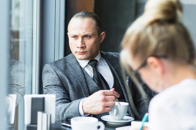 Hombre de negocios contemplado con taza de té sentado en el restaurante