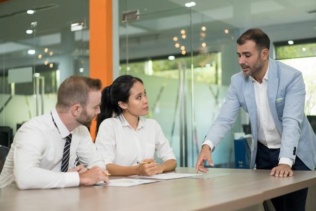 Hombre de negocios de pie y discutir problemas con colegas
