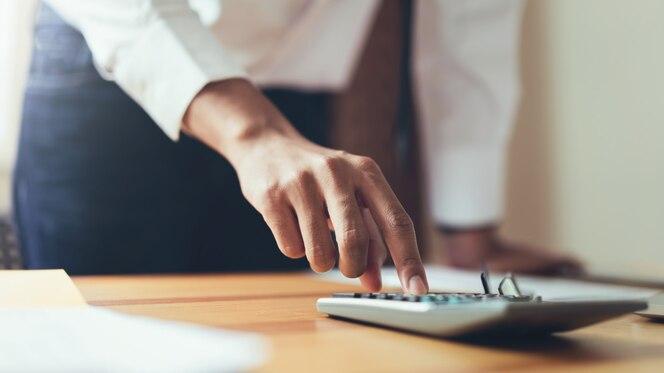 Hombre de negocios en la oficina y uso de computadora y calculadora para realizar la contabilidad financiera.