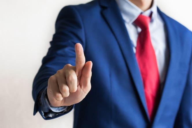 Hombre de negocios en traje profesional tocando la postura de pantalla virtual