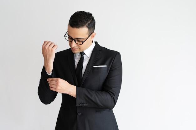 Hombre de negocios joven de moda serio abrochando el puño de la chaqueta.