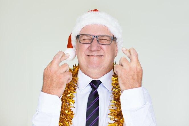 Hombre de negocios mayor, en, santa, sombrero, cruce, dedos