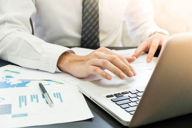 Hombre de negocios que analiza cartas de la inversión y que usa la tableta en el escritorio.