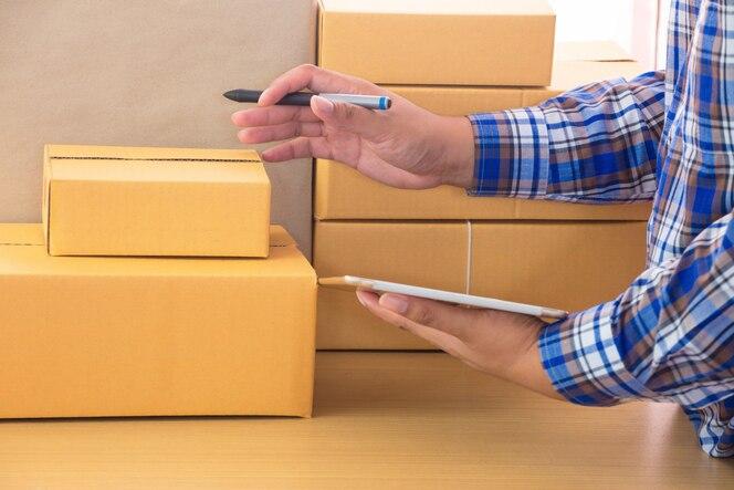 Hombre de negocios que trabaja con el teléfono móvil y el embalaje parcelas marrones caja en la oficina en el hogar