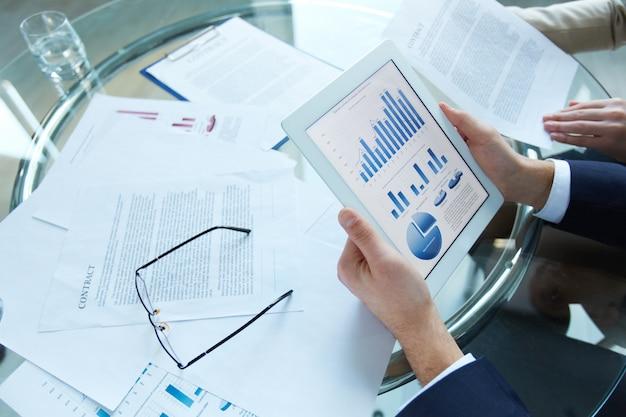 Hombre de negocios sosteniendo una tableta con datos estadísticos