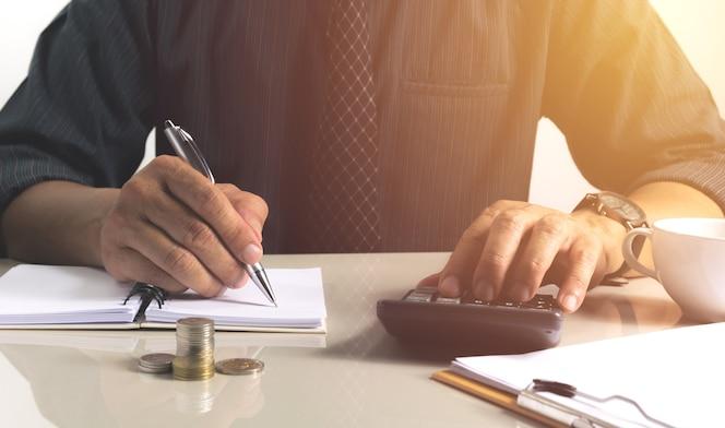Hombre de negocios trabajando y escribiendo en el cuaderno para los negocios con financiero y contabilidad