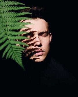 Hombre debajo de hojas verdes