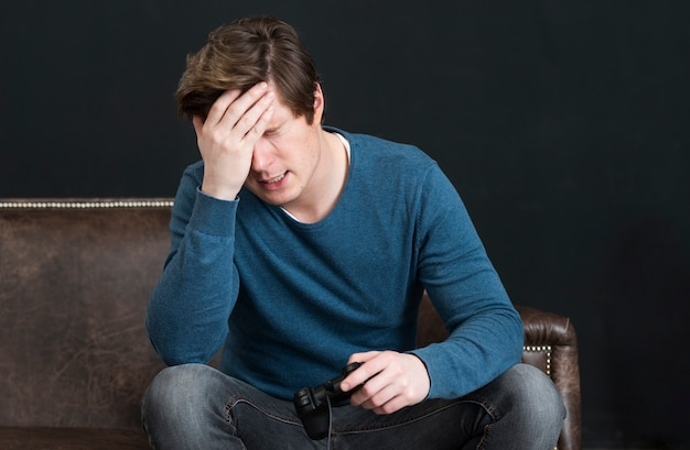 Hombre decepcionado jugando videojuegos