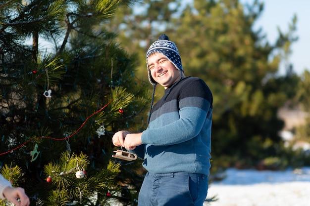 El hombre decora con un juguete decorativo y guirnalda de un árbol de navidad verde en la calle en el invierno en el bosque
