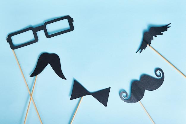 Hombre decorativo con bigote y gafas negras sobre un papel azul claro.