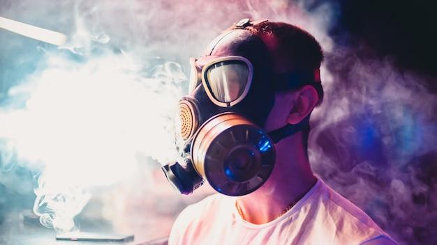 El hombre deja que las nubes de cachimba fumen en una máscara de gas