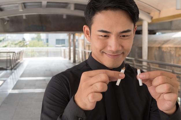 El hombre dejó de fumar, rompiendo el cigarrillo, concepto de decisión de estilo de vida saludable