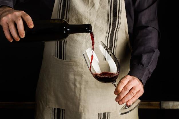 Hombre con un delantal sirviendo una copa de vino tinto