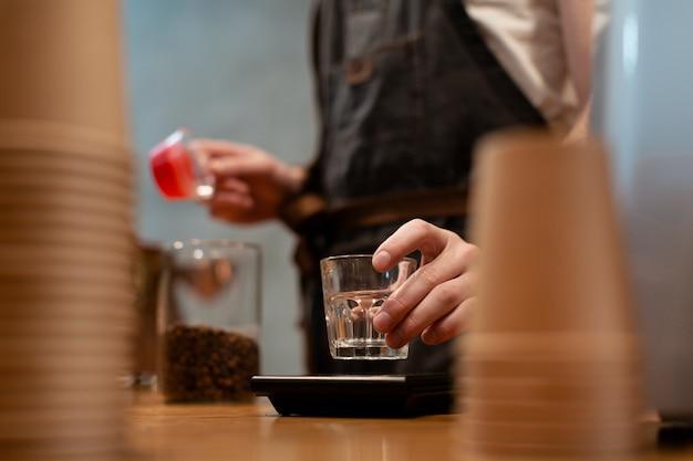 Hombre en delantal con vaso con tazas de café