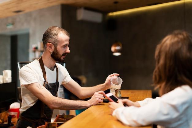 Hombre con delantal vertiendo agua en cafetera