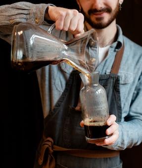 Hombre con delantal vertiendo café en frasco