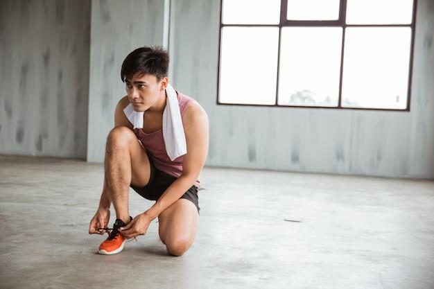 Hombre deporte atar sus zapatos antes de entrenar
