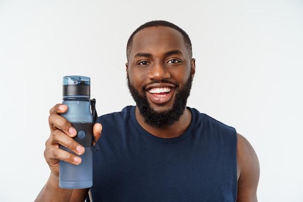 Hombre de deporte atleta masculino afroamericano con correr deportes con teléfono móvil y beber agua de botella.