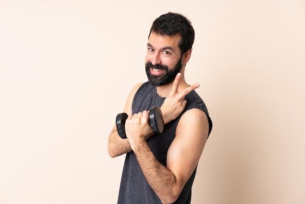 Hombre de deporte caucásico con barba haciendo levantamiento de pesas sobre la pared sonriendo y mostrando el signo de la victoria