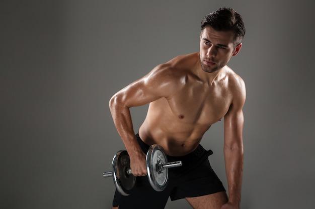 Hombre de deporte concentrado joven fuerte hacer ejercicios deportivos