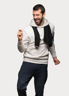 El hombre del deporte disfruta del baile mientras escucha música en una fiesta sobre un fondo gris aislado