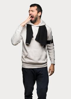 El hombre del deporte que bosteza y que cubre la boca abierta con la mano sobre fondo gris aislado