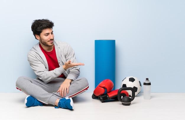 Hombre del deporte que se sienta en el piso que presenta una idea mientras que mira sonriente hacia